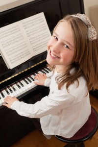 Photo of a young girl playing the piano at home. Sheet music has been altered to be unrecognizable.